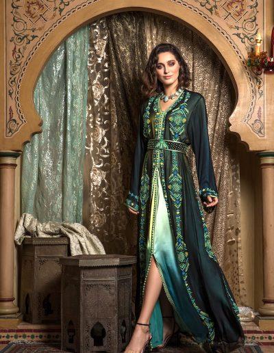 Tenue deux pièces en mousseline noire perlée multicolore sur le devant et les manches, portée sur un satin de soie en camaïeux de bleu fini de Aâkad. Ceinture coordonnée.